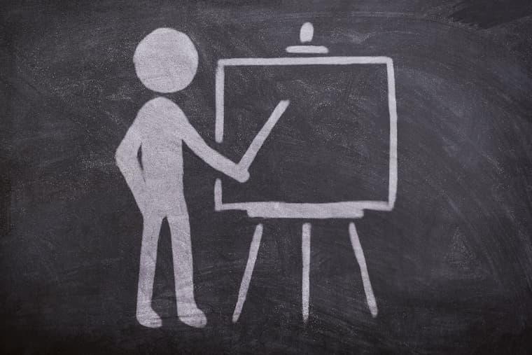 黒板でボードを指す人の画像