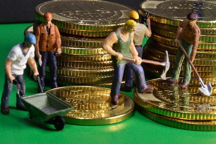 お金の上で人形が工事する画像