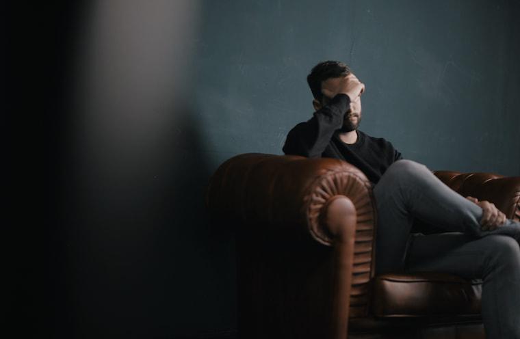ソファで悩む人の画像
